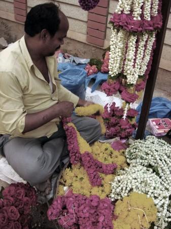 Шекхар вяжет цветочные гирлянды у храма, Бангалор, Индия. Он чувствует себя счастливым, потому что его профессия приносит радость людям. Фото: Tarun Bhalla