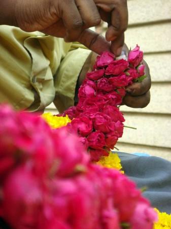 Шекхар вяжет гирлянду из роз у храма. Это ремесло передаётся из поколения в поколение. Фото: Tarun Bhalla