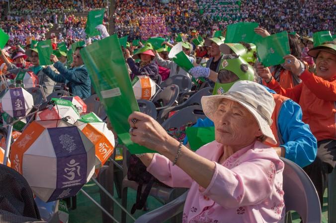 Корейские буддисты танцуют и радуются в преддверии фестиваля на встрече в университете Dongguk в центре Сеула. Буддисты со всей страны съехались сюда накануне парада. Фото: Jarrod Hall/Великая Эпоха (The Epoch Times)