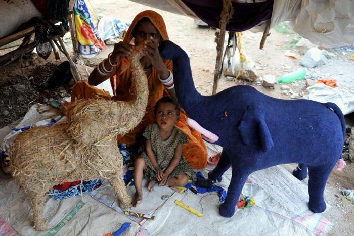 Ребёнок наблюдает, как мастерица изготавливает травяное чучело слона во временном дорожном навесе в Хайдарабаде, 8 июля 2011 года. Большинство индийцев используют такие игрушки для украшения своих домов. Фото: Noah Seelam / AFP / Getty Images / AFP / Getty Images