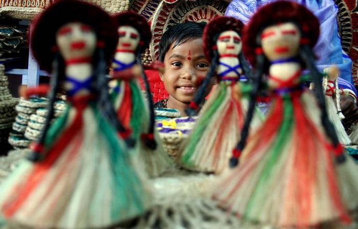Маленький ребёнок смотрит сквозь ряды джутовых кукол, представленных на ежегодной ярмарке изделий кустарного производства в Силигуре, 16 декабря 2007 года. Ежегодно тысячи производителей товаров и продавцов принимают участие на 15-дневной ярмарке. Фото: Diptendu Датта / AFP / Getty Images
