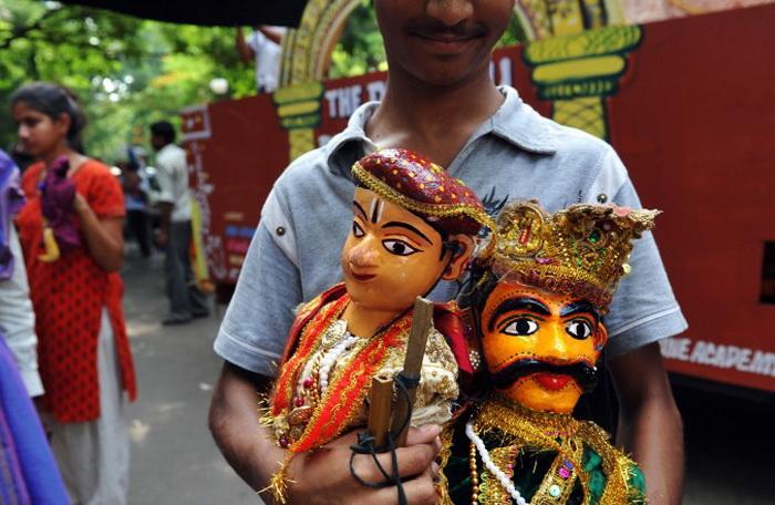 Индийский юноша держит в руках куклы во время собрания в Бангалоре 10 мая 2010 года. Собрание было организовано, чтобы обсудить ситуацию с угасающей традицией местных кукольных представлений и мастерства изготовления кукол среди населения. Фото: Dibyangshu Саркар / AFP / Getty Images
