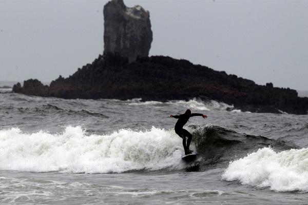 Серфингист плывет вдоль пляжа Индиан недалеко от Кэннон Бич, штат Орегон, 30 июля. Фото: Rick Bowmer