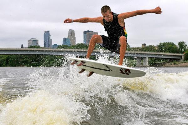 Чейз Хазен плывет на фоне силуэта Миннеаполиса во время Чемпионата мира по вейксерфингу на реке Миссисипи 22 июля. Вейксерферы стартуют с помощью веревки, а плывут по волне, образованной лодкой. Фото: Jim Mone