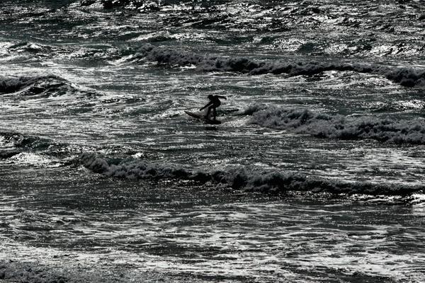 Серфер на длинной доске из Ассоциации профессионалов серфинга плывет в водах у пляжа Фистрол в Ньюквэе, Англия, 5 августа. Фото: Matt Cardy/Getty Images