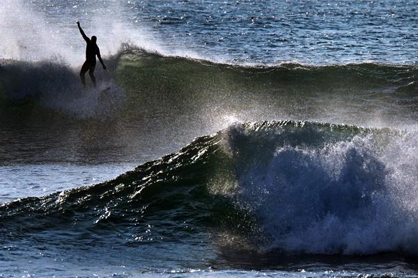 Серфингист оседлал волну рано утром вдоль берега недалеко от Скитуате, штат Массачусетс, 4 сентября. Фото: David L Ryan