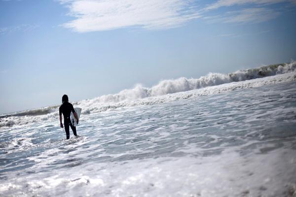 Серфингист входит в воды Лонг-Бич, штат Нью-Йорк, 19 сентября. Фото: David Goldman