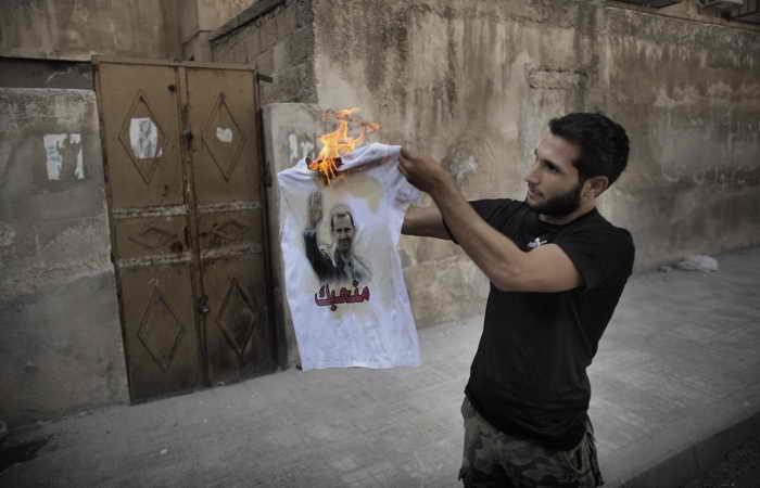 Сирийский повстанец сжигает футболку с портретом президента Башара Асада 12 сентября 2012 г. в Саиф аль-Даула, в окрестностях Алеппо. Фото: MARCO LONGARI/AFP/GettyImages