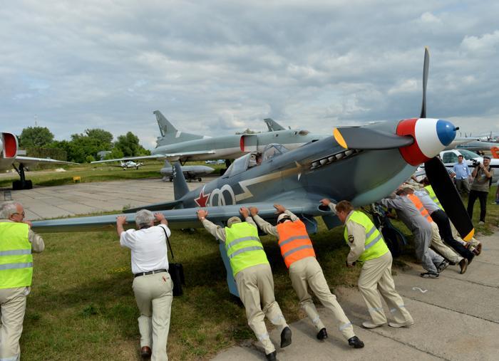 Сотрудники музея двигают истребитель Як-3, прибывший на фестиваль ретро-самолётов в музей авиации Киева 1 июля 2013 года. Фото: SERGEI SUPINSKY/AFP/Getty Images