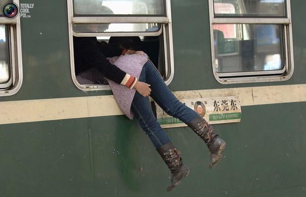 Пассажирка в окне поезда на станции в Хэфэе, провинция Анхой. Транспортная система Китая всегда работает на всю в период отпусков и новогодних праздников. Фото:bigpicture.ru