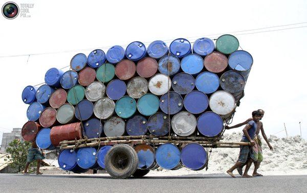 Бангладешские рабочие тянут телегу с бочками на рынок в Дакке. Фото:bigpicture.ru