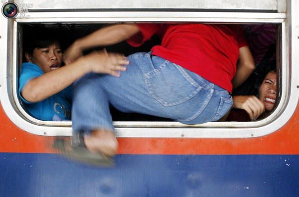 Пассажир запрыгивает в окно переполненного поезда на станции в Джакарте. Миллионы жителей Джакарты набиваются в поезда как сельди в бочку каждый год в преддверии мусульманского праздника Курбан-байрам, означающего окончание месяца Рамадан. Фото:bigpicture.ru
