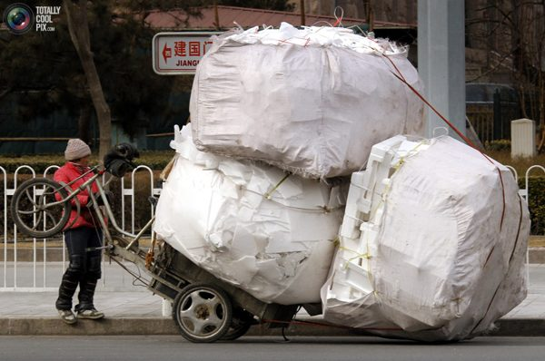 Сборщица материалов, идущих на переработку с перегруженным велосипедом на главной улице Пекина. Фото:bigpicture.ru