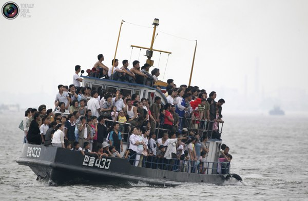 Жители Северной Кореи смотрят на китайскую туристическую лодку на реке Ялу, недалеко от корейского города Синыйджу. Фото:bigpicture.ru