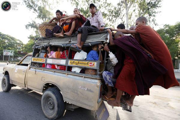 Новоиспеченные буддистские монахи зацепились за грузовичок с пассажирами в центре Мандалая. Фото:bigpicture.ru