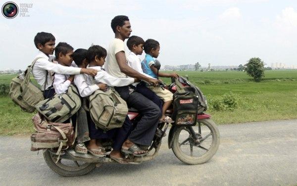 Мужчина на мотоцикле с шестью детьми по пути из школы домой в северо-индийском штате Уттар-Прадеш. Фото:bigpicture.ru