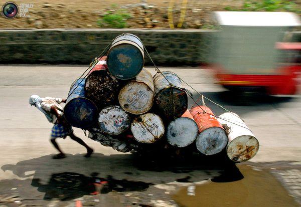 Индийский рабочий с перегруженной телегой на дороге в городе Бомбей. Сотни миллионов индийцев, включая детей и пожилых людей, вынуждены выживать на менее чем 1 доллар в день. Фото:bigpicture.ru