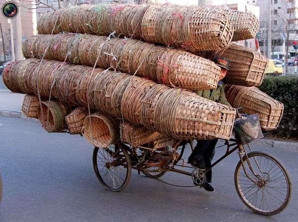 Курьер практически не виден за бамбуковыми корзинами на велосипеде в Пекине. Этот мужчина не может позволить себе автомобиль или грузовик, так что вынужден обходиться велосипедом, который он купил за 450 юаней. Мелкие грузовые перевозки на велосипедах очень распространены в Китае. Фото:bigpicture.ru