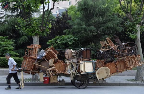 Торговец с телегой, переполненной плетеными стульями на улице Шанхая. Фото:bigpicture.ru