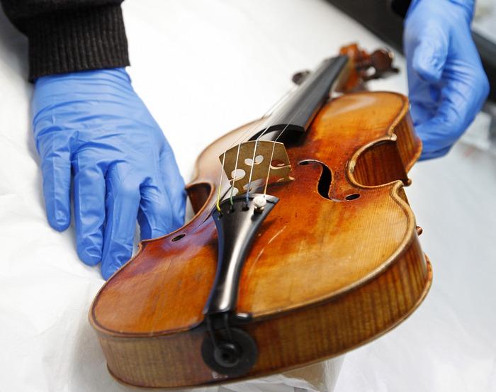 Французский химик проверяет скрипку Страдивари в научно-исследовательской лаборатории Музея de la Musique в Париже, 3 декабря 2009 года. Фото: PATRICK KOVARIK/AFP/Getty Images