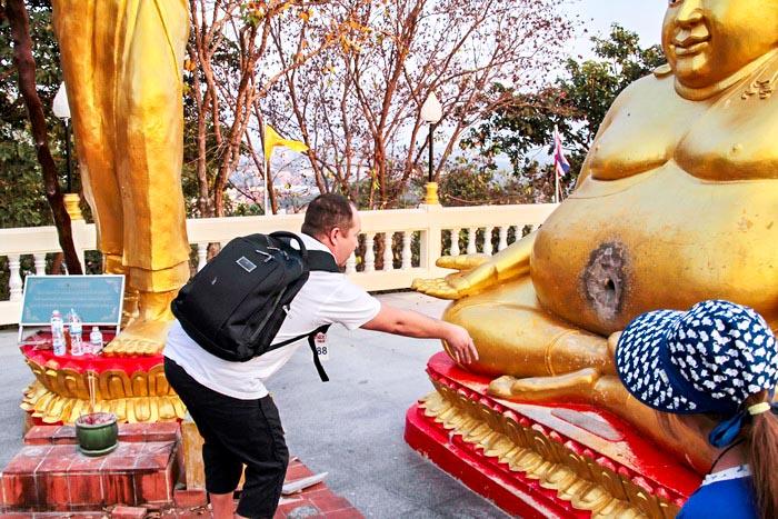 Мужчина пытается попасть монеткой в отверстие статуи Будды. Отдых в Паттайя. Фото: Николай Карпов/Великая Эпоха (The Epoch Times)