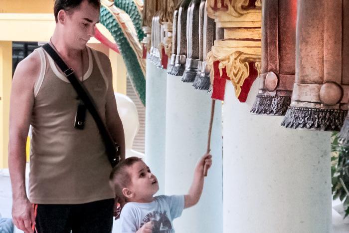 Мальчик с папой звонит в колокольчики, чтобы очиститься от кармы. Отдых в Паттайя. Фото: Николай Карпов/Великая Эпоха (The Epoch Times)
