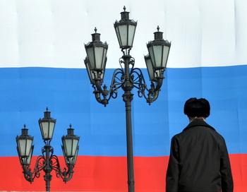 Человек перед большим русским флагом в Москве. Фото: SERGEI SUPINSKY/AFP/Getty Images