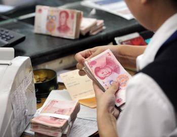 Сотрудница китайского банка перещитывает денежные купюры клиента. Фото: STR/AFP/Getty Images