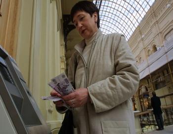 Женщина считает деньги после снятия наличных денег из банкомата. Фото: Oleg Nikishin / Getty Images