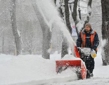 Сотрудник коммунальных служб убирает снег на одной из улиц города. Фото РИА Новости