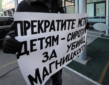 Плакат против принятия закона о запрете усыновления американцами российских детей держит лидер оппозиции Борис Немцов у здания Госдумы, 19 декабря 2012 года. Фото: ANDREY SMIRNOV/AFP/Getty Images