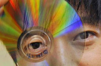 Джеймс Чон из технологического университета Свинбурн города Мельбурна демонстрирует DVD, который может сохранить данные в пятикратном размере, то есть вмещает в себя более чем 2000 фильмов  на одном диске. Фото: William West /AFP/Getty Images