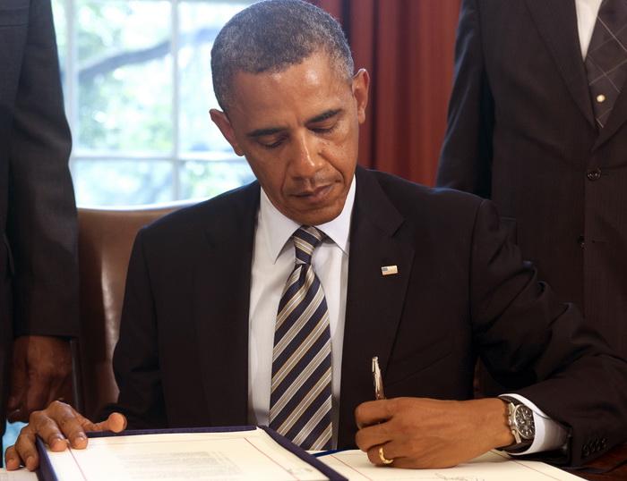 Президент США Барак Обама подписывает документы в Овальном кабинете Белого дома в Вашингтоне, округ Колумбия, 6 августа 2012 года. Фото: SAUL LOEB/AFP/GettyImages