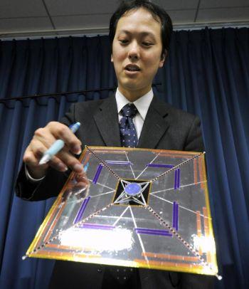 Юичи Цуда, ученый-исследователь Японского аэрокосмического  агентства по изучению космоса (JAXA) показывает модель японского спутника IKAROS  (Межпланетный корабль в виде воздушного змея, ускоряемый за счет солнечной радиации) на пресс-конференции в Токио 27 апреля 2010 года. Фото: Yoshikazu TSUNO/AFP/Getty Images