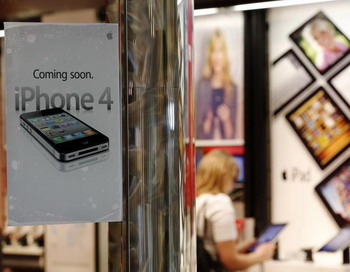 Покупательница в магазине Verizon рассматривает Apple iPad, на стекле рекламка о скором выходе Verizon iPhone. 3 февраля 2011, Орем, штат Юта, США. Фото: George Frey/Getty Images