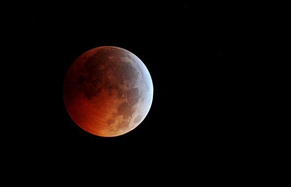 День зимнего солнцестояния впервые за 400 лет совпало с полным лунным затмением. Фотообзор. Фото: DON EMMERT, KAREN BLEIER/AFP/Getty Images