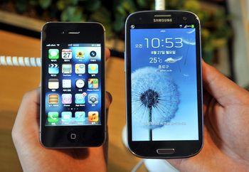 iPhone 4S от Apple (слева) и Samsung Galaxy S3 (справа) в магазине мобильных телефонов в Сеуле 27 августа 2012 года. После вердикта американского суда, акции Samsung Electronics понизились на 6,75%. Фото: JUNG YEON-JE/AFP/GettyImages