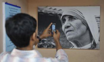 Мальчик фотографирует изображение Матери Терезы, который висит на стене вагона «Экспресс Матери» в Мумбаи. Мать Тереза служила бедным, больным, сиротам и обездоленным более 47 лет. Исследователь из Британской Колумбии (Канада) обнаружил, что наблюдение милосердия вдохновляет других делать добро в своей жизни. (Sajjad Hussain/AFP/Getty Images)