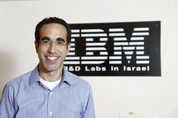 Ади Шахарабани, старший эксперт по безопасности данных в IBM, позирует на фоне логитипа компании своего офиса с Израиле. Фото: Великая Эпоха (The Epoch Times)