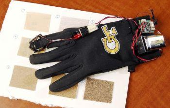 Перчатка с приводом для генерации высокочастотных колебаний и девять образцов наждачной бумаги. Фото: Georgia Tech/Gary Meek