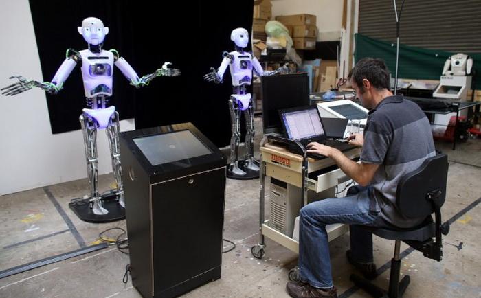 Дизайнер и инженер компании Engineered Arts Маркус Холд работает над двумя почти собранными роботами RoboThespian 30 июля 2013 года в Пенрине, Великобритания. Фото: Matt Cardy/Getty Images