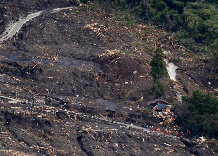 Спасатели ищут выживших в результате оползня вызванного проливными дождями тайфуна Wipha на острове Осима, в 120 км к югу от Токио. Фото: JIJI PRESS/AFP/Getty Images