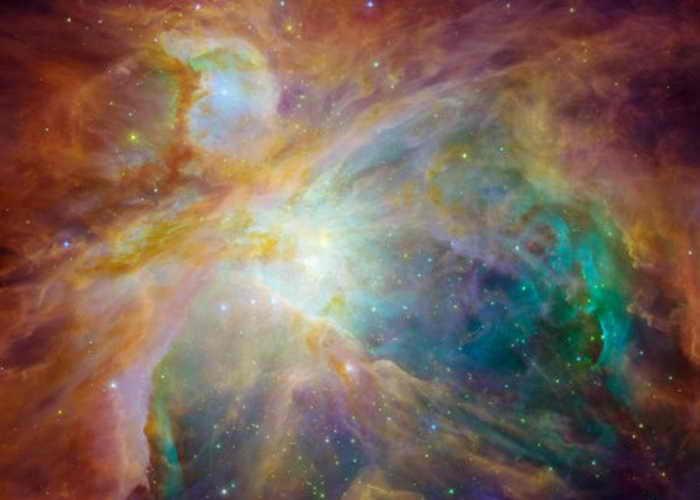 Четыре массивные звезды в центре изображения, полученного космическими телескопами «Спитцер» и «Хаббл» НАСА. Молодые звёзды обозначены оранжево-жёлтыми точками, рассредоточенными по туманности. Фото: NASA