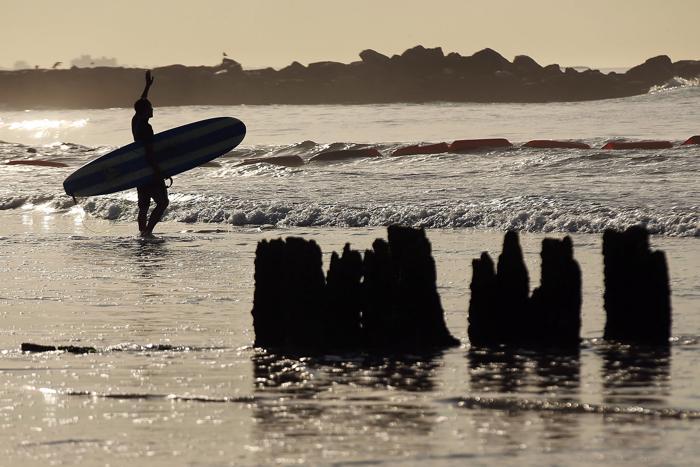 Сёрферы вышли 31 июля 2013 года опробовать волны на пляжи Нью-Йорка, разрушенные ураганом. Фото: Spencer Platt/Getty Images