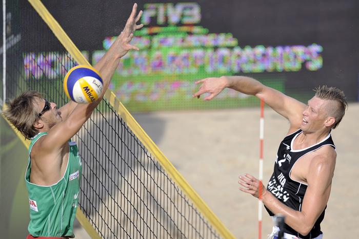 Ярослав Кошкарёв и американец Кейси Паттерсон (п) на третьей встрече группового этапа чемпионата мира по пляжному волейболу в Польше 4 июля 2013 года. Фото: Adam Nurkiewicz/Getty Images