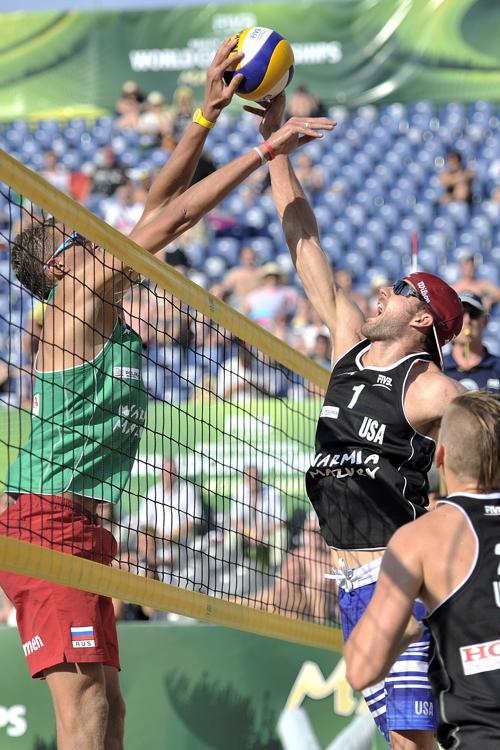 Константин Семёнов (л) и американец Джейкоб Гибб (п) на третьей встрече группового этапа чемпионата мира по пляжному волейболу в Польше 4 июля 2013 года. Фото: Adam Nurkiewicz/Getty Images