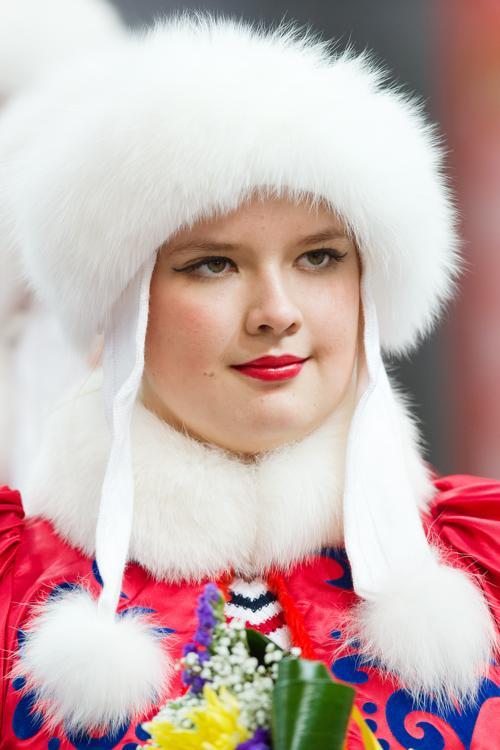 Девушка в традиционном костюме принимает участие во вручении медалей и цветов. Фото: LEON NEAL/AFP/Getty Images