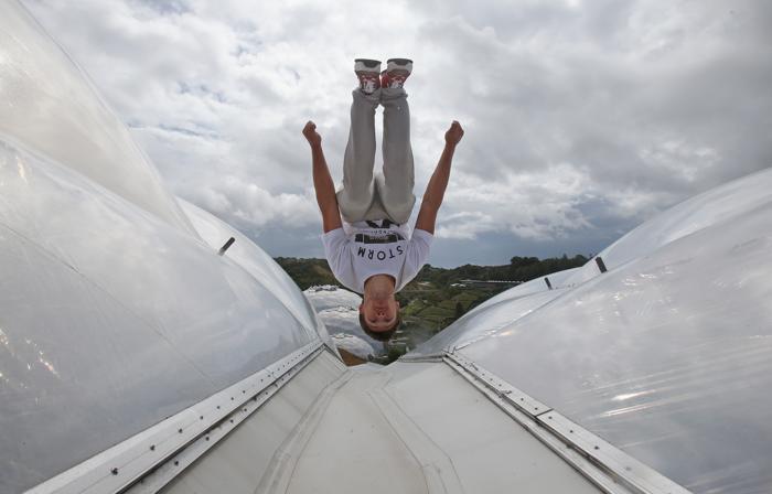 Профессиональные паркуровцы и фрираннеры Тим Шейф и Пип Андерсен выступили в тропических биомах экологического парка «Рай» (Eden Project) в Корнуолле (Англия) 29 июля 2013 года. Фото: Matt Cardy/Getty Images