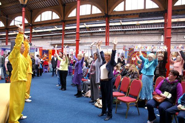 Практикующие Фалуньгун обучают упражнениям посетителей выставки здоровья в Дублине. Фоторепортаж. Фото с сайта  minghui.org