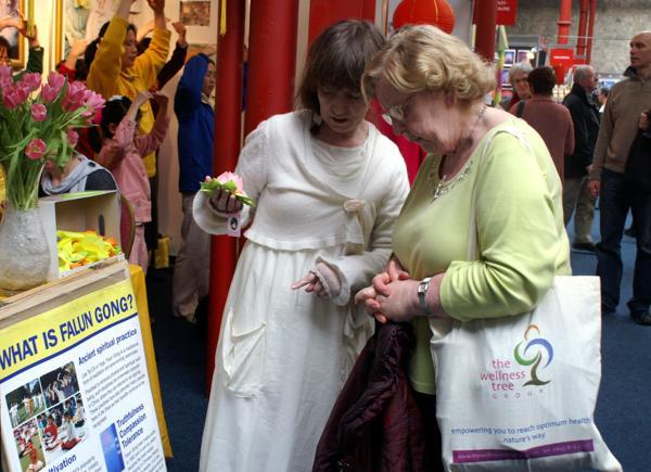 Практикующая рассказывает посетительнице выставки здоровья о Фалуньгун. Фоторепортаж. Фото с сайта  minghui.org